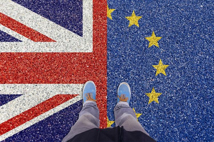 Bandiera Europea e bandiera inglese divise a metà sul pavimento con un ragazzo che tiene un piede a destra e uno a sinistra sulle bandiere.