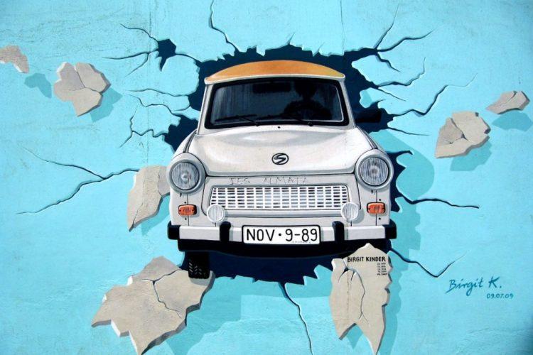 Street art di una trabant, tipica auto tedesca, che rompe il Muro di Berlino