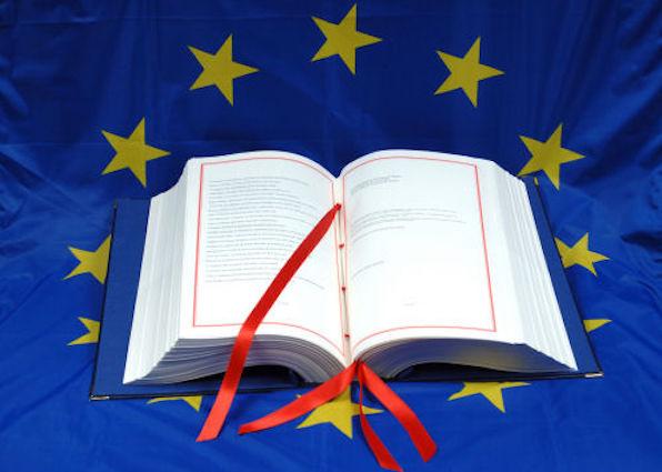 libro bianco in primo piano con sfondo la bandiera dell'unione europea