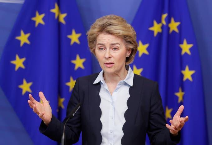 Donna che tiene un discorso con due bandiere dell'Unione Europea alle spalle