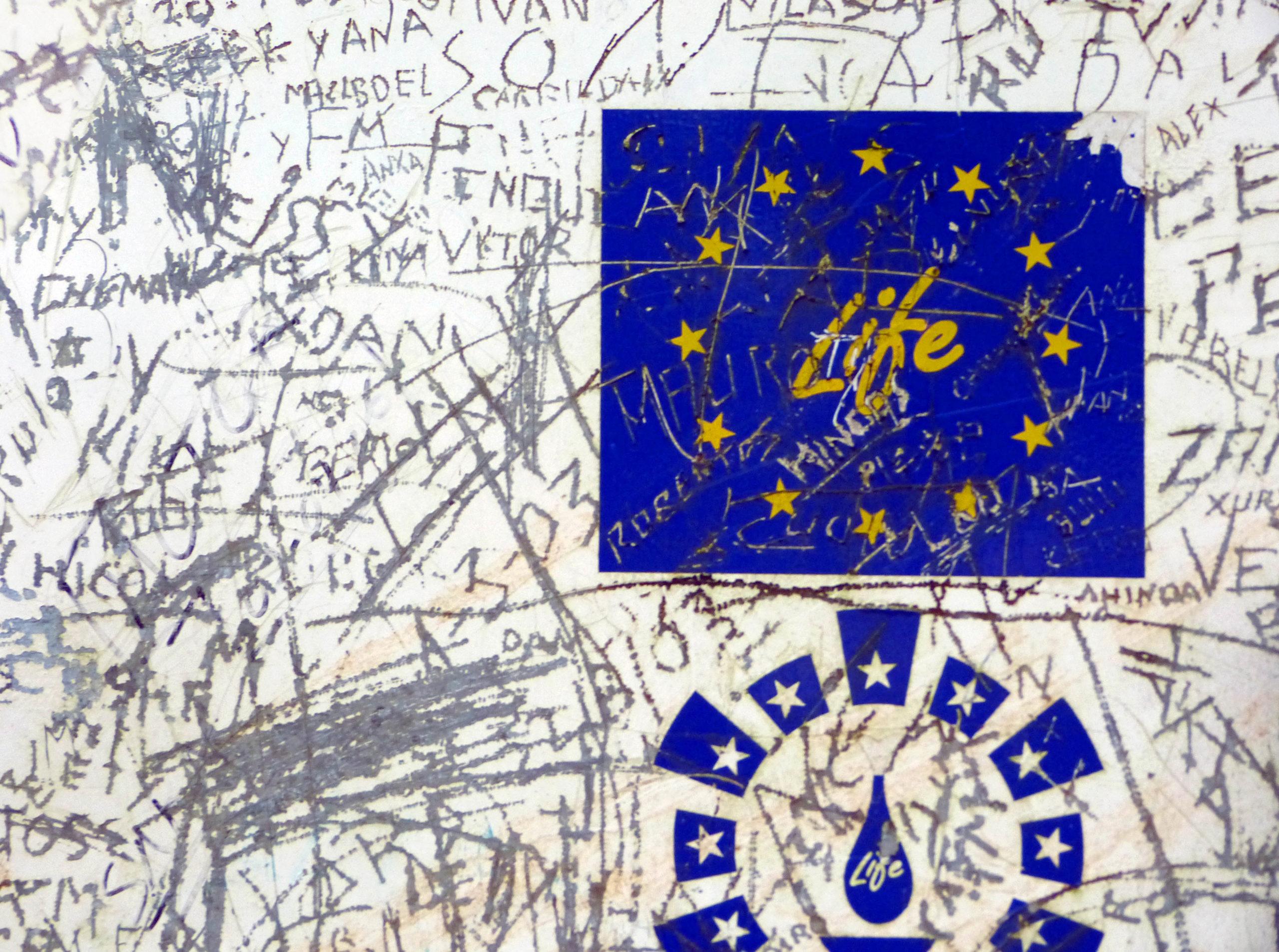 Muro con graffiti con in primo piano la bandiera dell'Unione Europea