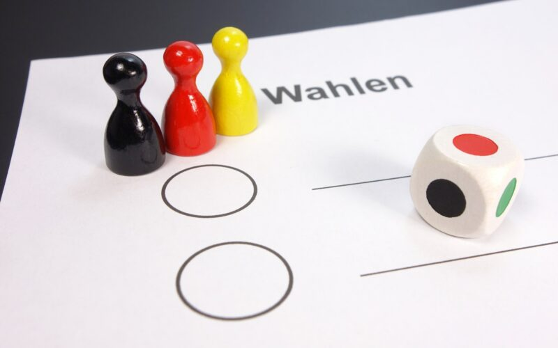 foglio per le elezioni con sopra un dado e tre pedoni colorati come la bandiera tedesca